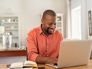 smiling black man working on his computer to refinance his mortgage